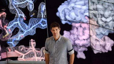 Dr Berry standing in front of images detailing the structure of the CMV protein.