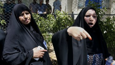 Families of newborn babies who died in the fire gather outside Yarmouk hospital.