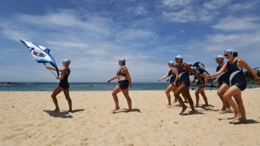 Coogee Surf Club members brave the heat to compete in the march past at the Surf Life Saving Carnival at Coogee Beach.