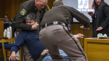 Sheriff's deputies restrain Randall Margraves in a Michigan court room after he tried to attack disgraced doctor Larry Nassar.