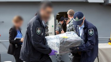 Australian Federal Police officers carry bags of cocaine.