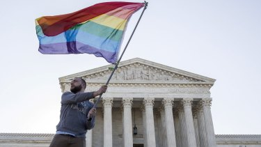 Vin Testa waves a gay rights flag in front of the Supreme Court.