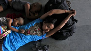 A passenger and her children sleep at a railway station in Allahabad, where temperatures reached 46.4 degrees this week.