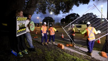 Protesters chained themselves to trees on Alison Road on Thursday night as workers erected fences.