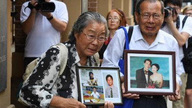 Min Lin's parents, Feng Qing Zhu (left) and Yang Fei Lin, outside the Supreme Court with photos of their murdered family members on Friday.