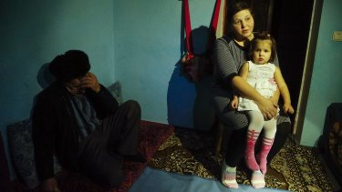 Elnara, the wife of arrested Tatar protester Ali Asanov, sits with one of her daughters, Mumine, in her home in the village Urozhayne, Crimea.
