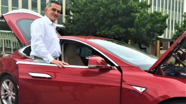Rene Konrad with charges his Tesla electric car at home with energy from his solar panels.