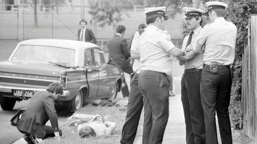 Detectives watch over handcuffed suspect after a bank robbery in Coolaroo, Melbourne in 1977. The men were arrested after a high-speed police chase and gun battle.