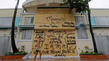 A beachgoer walks by a boarded restaurant at Miami Beach in anticipation of Hurricane Irma.