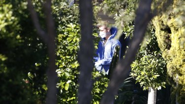 A forensic worker at the Glenfield house where a 15-year-old boy was shot in the head.
