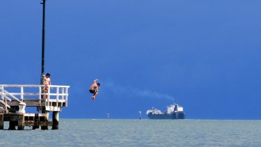 Young men jump from a pier into Port Phillip Bay.