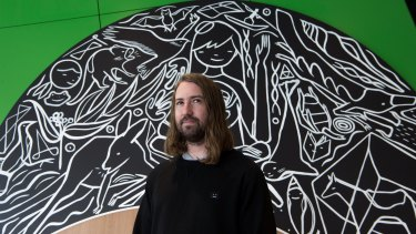 David Booth (aka Ghostpatrol) in front of one the murals he has painted for the new Pauline Gandel Children's Gallery at Melbourne Museum.