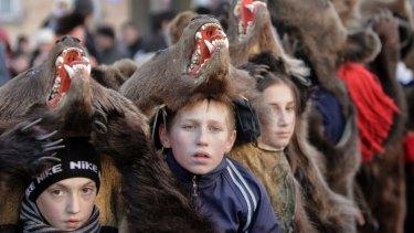 Children wear bear furs during New Year ritual dances in Romania.