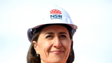Premier Gladys Berejiklian in a hard hat bearing the NSW government's Waratah logo.