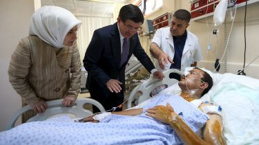 Turkish Prime Minister Ahmet Davutoglu (second from left) visits a survivor of the attack.