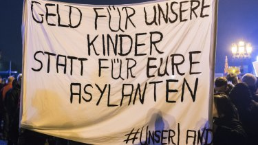 """Protesters hold a banner during a Pegida demonstration. The banner reads in German: """"Money for our children and not for your asylum seekers."""""""