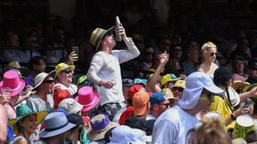 A man in the crowd at the MCG does a 'shoey'.