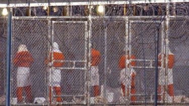 Detainees at Camp X-Ray face Mecca during evening prayers.