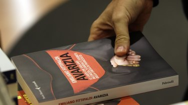 """Italian journalist  Emiliano Fittipaldi holds his book """"Avarice"""" in Rome on Tuesday."""