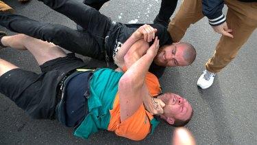 Rival protesters wrestle.