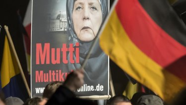 A banner reading 'Mum multiculti' and depicting a manipulated image of German Chancellor Angela Merkel is carried by a protester behind the German flag as thousands of people join a protest in Erfurt, central Germany, on Wednesday.