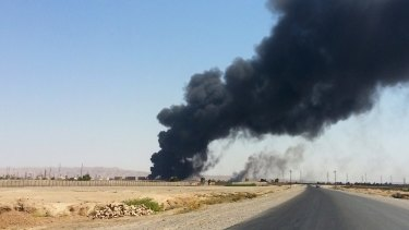 Smoke rises from the Baiji refinery in June.