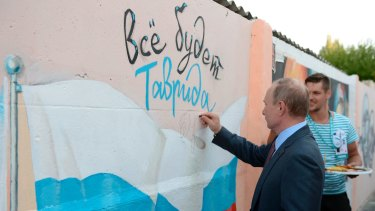 Russian President Vladimir Putin signs  graffiti showing a Russian state flag and text reading 'All will be well. Tavrida', as he visits the youth educational forum 'Tavrida' in Crimea earlier this month.