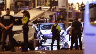 Police officers stand next to the van involved in an attack in Las Ramblas in Barcelona, Spain.