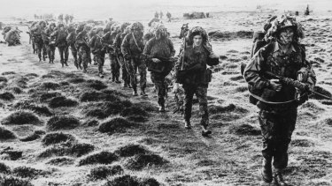 A line of British soldiers in camouflage advancing during the Falklands War.
