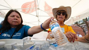 Salvation Army volunteers  restock a cooler with bottles of water at a hydration station in Phoenix.