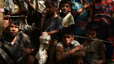 Rohingya refugee children wait at a Red Cross distribution point in Burma Para refugee camp.