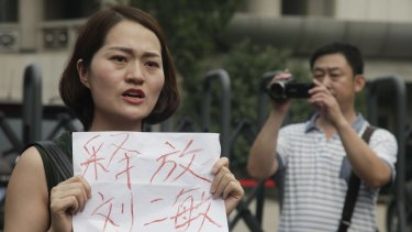 """Li Wenzu, wife of imprisoned lawyer Wang Quanzhang, holds a sign that reads """"Release Liu Ermin"""" outside the Tianjin court. Liu Ermin is the wife of one of the arrested activists."""