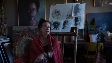 Artist Mirra Whale in her Marrickville studio, with sketches she made of Philip Nitschke.