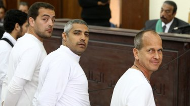 Mixed feelings about leaving his colleagues behind: Peter Greste (right) and co-defendants, Al-Jazeera English producer Baher Mohamed, left, Canadian-Egyptian acting Cairo bureau chief Mohamed Fahmy, centre.