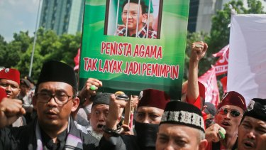 """Muslim protesters shout slogans as they hold up a placard with a picture depicting Jakarta governor Basuki """"Ahok"""" Tjahaja Purnama behind bars."""