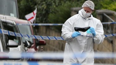 A forensics officer looks at a female shoe, at the scene after Labour MP Jo Cox was killed in an attack in her constituency.