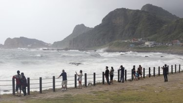 Visitors to a coastal park watch waves from approaching Typhoon Soudelor in Keelung.