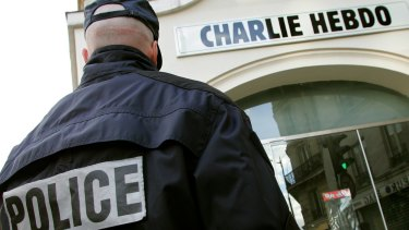A policeman stands guard outside the French satirical weekly <i>Charlie Hebdo</i> in Paris in this February 9, 2006 file photo. The magazine has been targeted by Islamists before.
