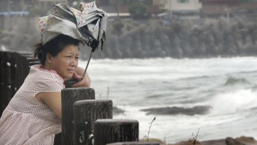 A woman braves the winds as she watches waves from approaching Typhoon Soudelor in Keelung, northeastern Taiwan,  on Friday