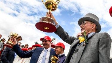 Almandin owner Lloyd Williams holds the Cup aloft, beside him jockey Kerrin McEvoy and trainer Robert Hickmott.