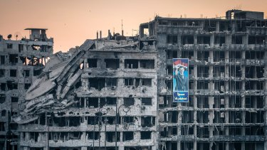 A poster of President Bashar al-Assad on a destroyed shopping mall in Homs, Syria.