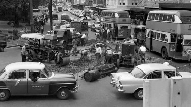 """But for Sydney motorists, even two years seems a long time to wait before they can expect a smoother ride..."" Traffic jams in Elizabeth Street on 12 December 1961, due to workmen removing tram tracks."