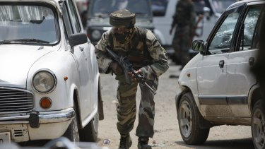 An Indian soldier takes cover behind cars in Dinanagar.