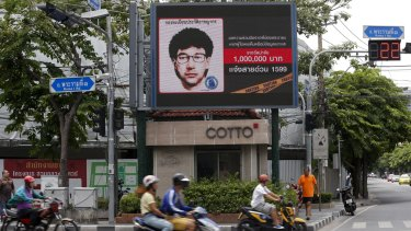 People ride past a digital billboard showing a sketch of the main suspect in the Erawan shrine bombing.