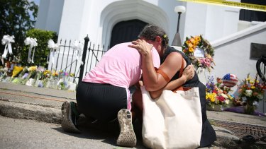 Women comfort each other as they mourn in front of the Emanuel African Methodist Episcopal Church after a mass shooting at the church that killed nine people in Charleston, South Carolina.