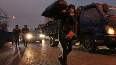 Zhou Xiaomei, 44, a house cleaner in Beijing, moves her belongings.