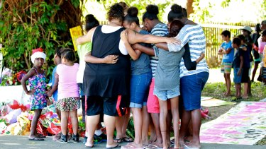 Mourners gather outside the Cairns house where eight children were murdered.