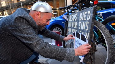 John McKenzie (aka IG McSporren) pastes a sign over a Jesus bike in the city.