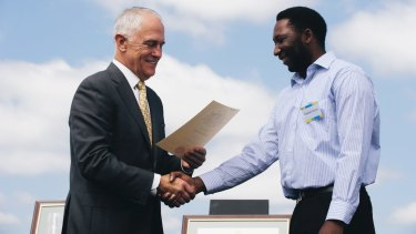 Prime Minister Malcolm Turnbull welcomes a new citizen at an Australia Day ceremony.