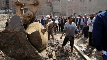 Egyptian workers lift parts of the statue with an excavator.